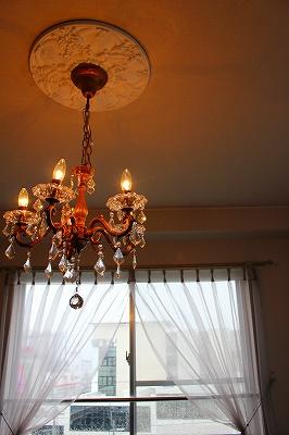 シャンデリアの向こうにレースのドレープカーテンの窓が写る室内の写真