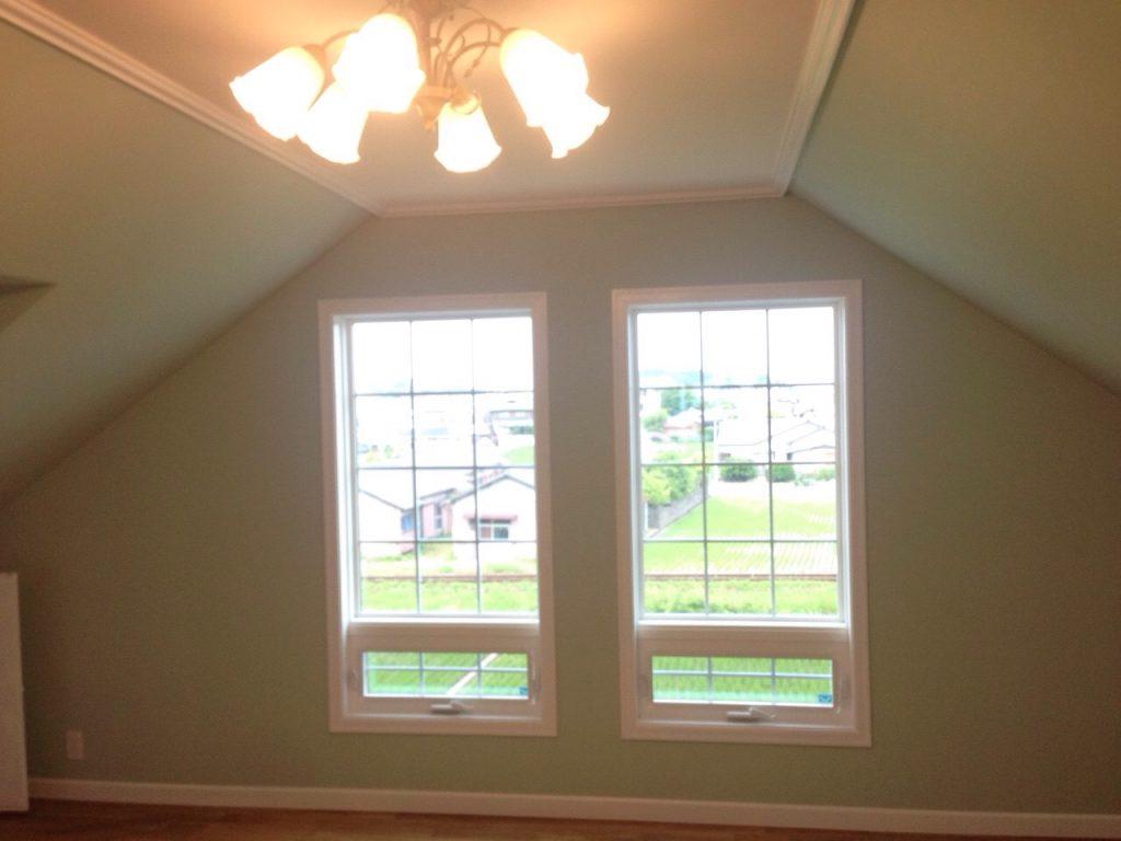 照明のついた部屋のカーテンのかかっていない2つの窓