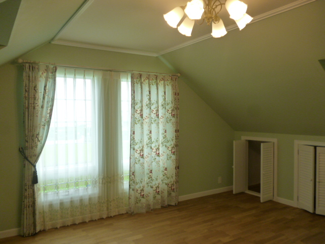 照明のついた部屋の2つの窓にカーテンがかけられた様子