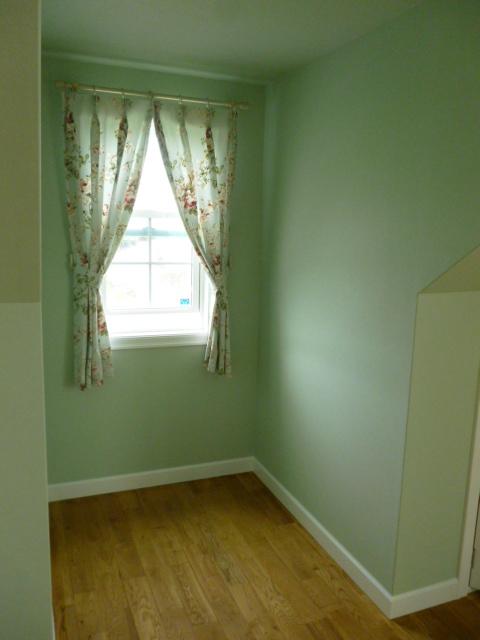 小窓にかかるミントグリーンに花柄のカーテン