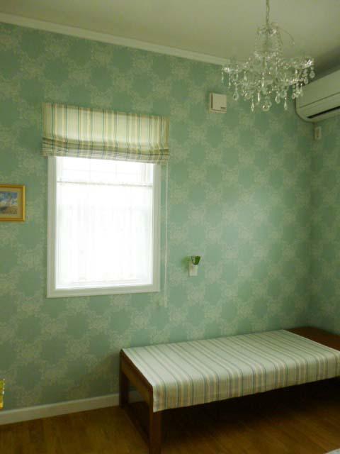 ストライプのシェードがかかる窓と部屋の様子