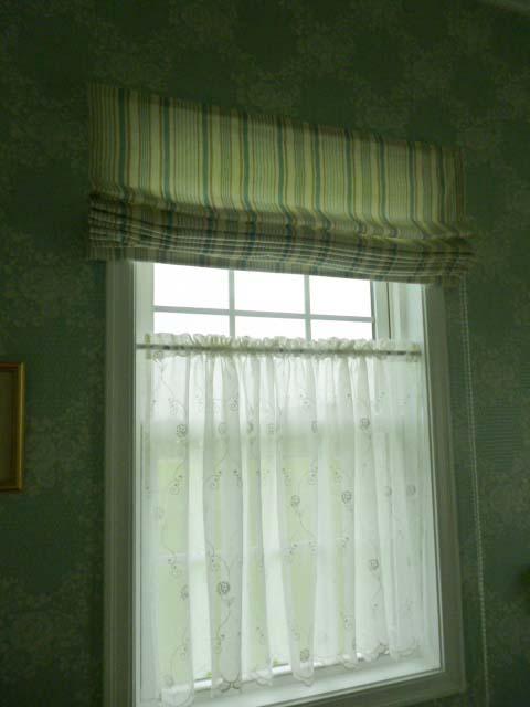 上部にストライプのシェードと中央に白いレースのカーテンのかかる窓