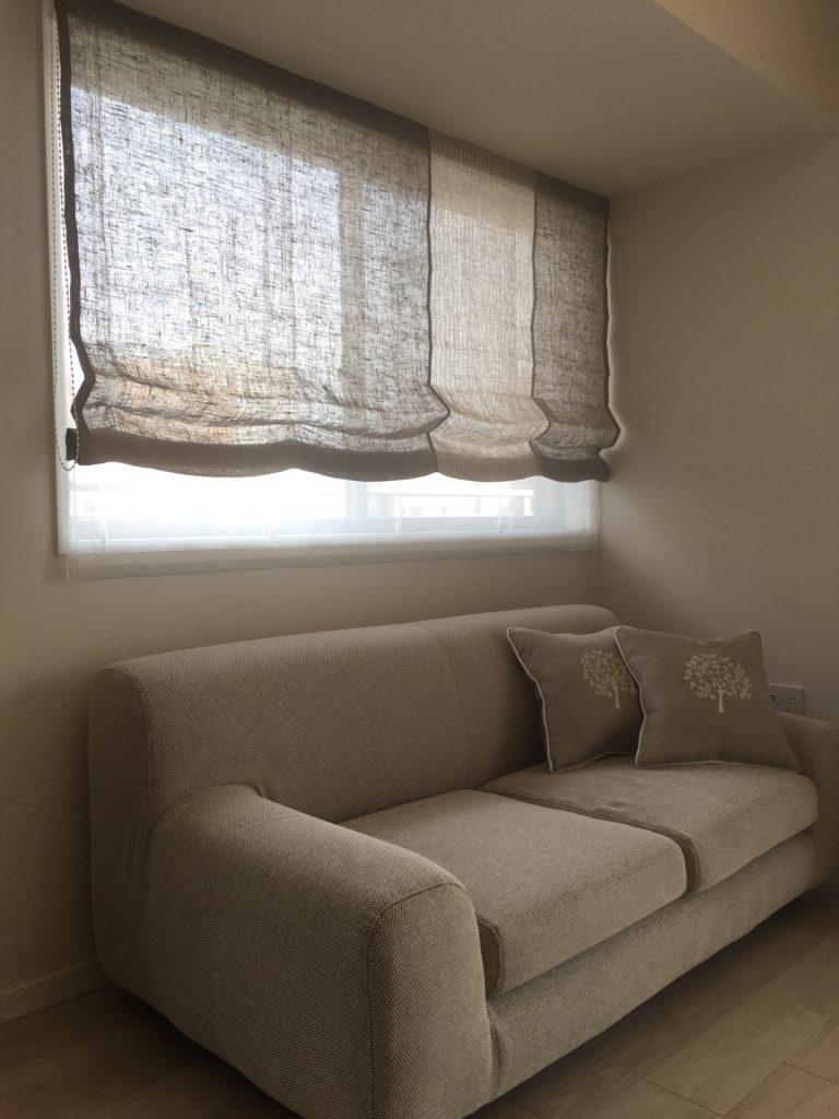 窓辺のソファーに2つのクッションが置かれている