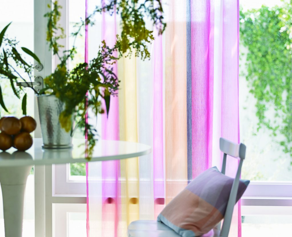 白いテーブルとイスの奥に、薄地のピンク系のカーテン