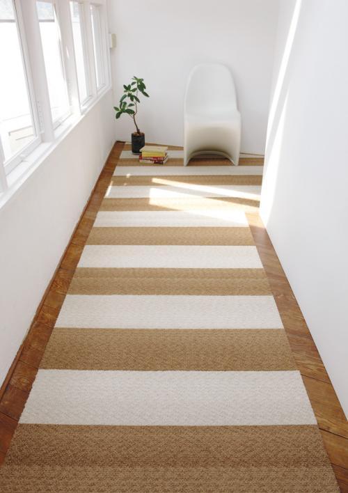 室内の廊下の写真、交互に茶色と白のパネルカーペットを敷いている。奥に椅子と本と観葉植物が置いてある。