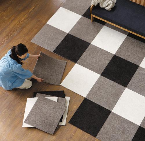 洋室を頭上から撮影した写真、滑り止め付きのパネルカーペットを敷いている女性がいる
