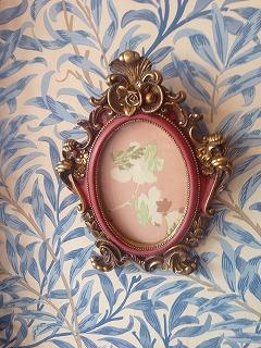 ピンク色の背景に白い花が描かれた壁飾り