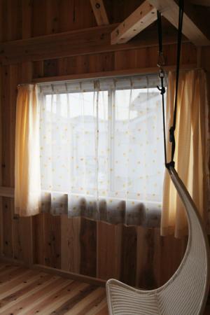 水玉模様のレースのカーテンが掛かった窓がある部屋。天井の梁からは椅子が釣り下がっている。