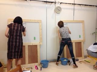 壁紙教室にて受講者が壁紙を貼っている作業写真