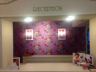 ピンクを基調とした花柄の壁紙を少し離れた所から撮った写真
