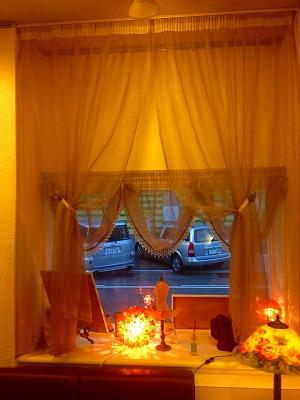 オレンジの光でライトアップされたドレープカーテンが掛かっている窓辺の写真