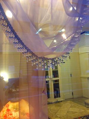 キラキラした飾り月のドレープカーテンが掛かった窓を屋外から撮った写真