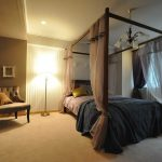 大きなベッドとソファー、スタンド照明が置かれた部屋