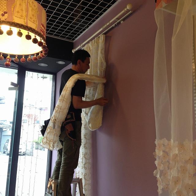 塗り替えたパープルの壁に男性がカーテンをかける様子