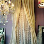 パープルの壁に白いカーテンを両開きにかけている様子