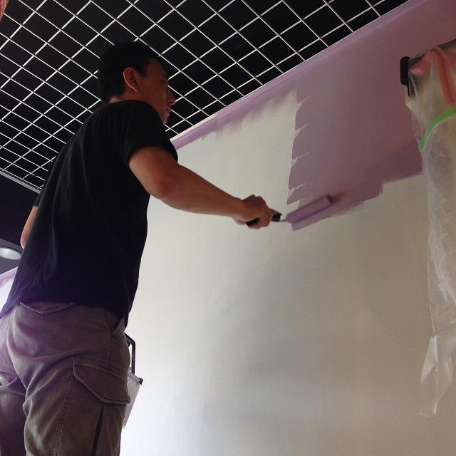 男性が壁をパープルに塗り替えている様子