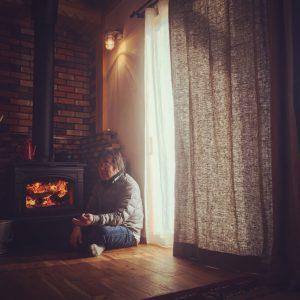 薪ストーブの近くに座る男性とカーテン。