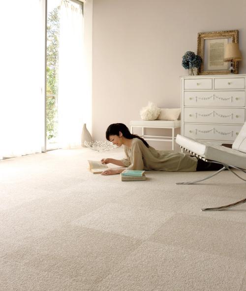白いパネルカーペットを敷き詰めた室内写真。中央にうつ伏せに寝そべりながら本を読む女性