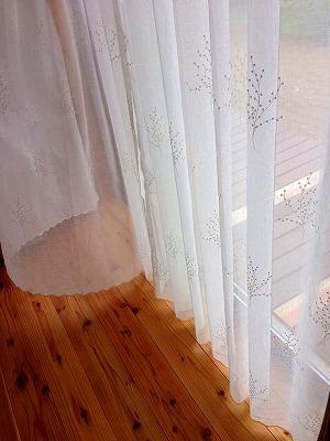 木の模様が入った白いレースのカーテンが掛かった窓辺