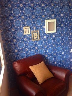 ブルーの壁の部屋の隅に茶色の一人掛けソファが置いてある写真