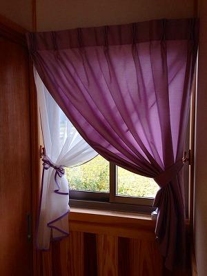 白いレースと紫のカーテンをドレープにしてとめた小窓