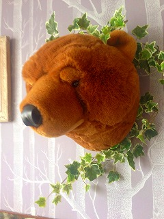 周りにフェイクグリーンをあしらった茶色のクマの顔の壁飾り