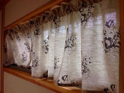 リネンのプリントカーテンが掛かった横長の窓