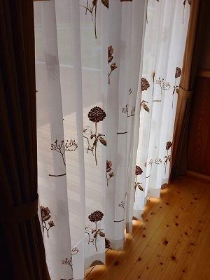 白地に茶色の花の刺繍が入ったカーテンがかかった窓辺