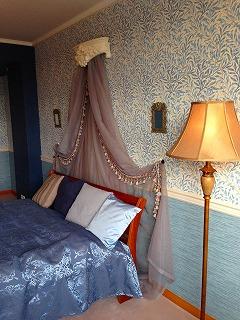 天蓋カーテンの下にブルーを基調としたベッドが置かれた寝室の写真