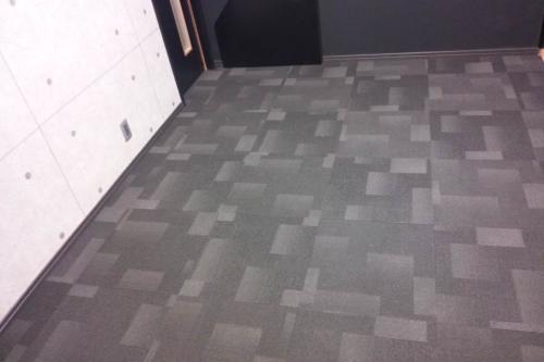 AVルーム写真三枚目、黒とグレーのモザイク調のタイルカーペットの床