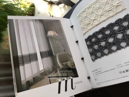 白い生地に黒が入ったカーテンの部屋が掲載されたページとサンプル生地
