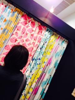 並んだカーテンを見る女性の後ろ姿