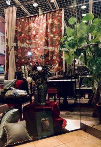店内の写真、中央にアンティーク調の花瓶、天井から吊り下げられたクロス、家具やクッションなど