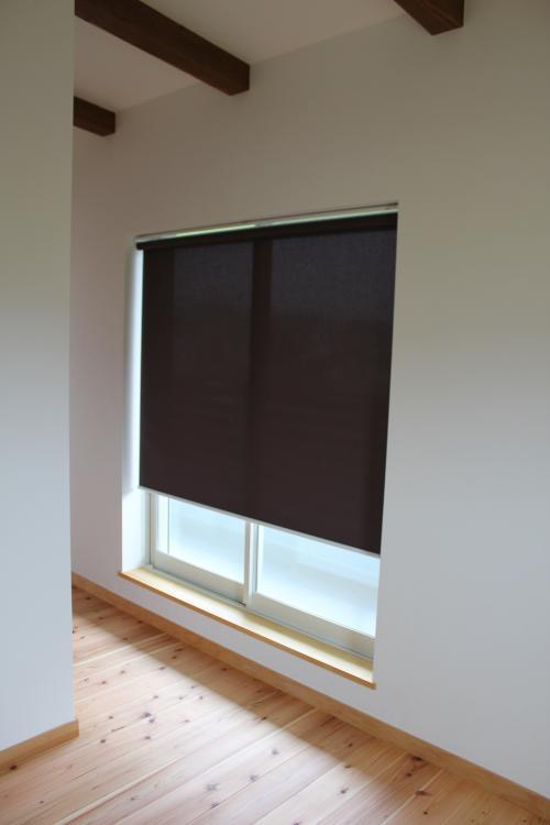 大きな窓に付けられた黒いロールスクリーン