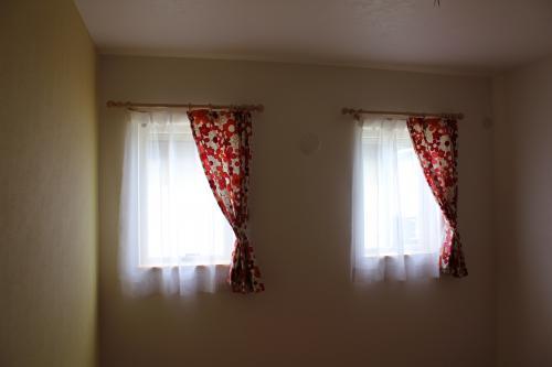 赤いプリント柄のカーテンの窓が2つ