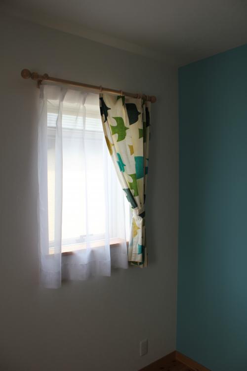 グリーン系のプリント柄のカーテンが掛かった窓