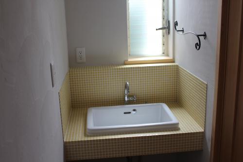 黄色のタイルを貼った洗面所