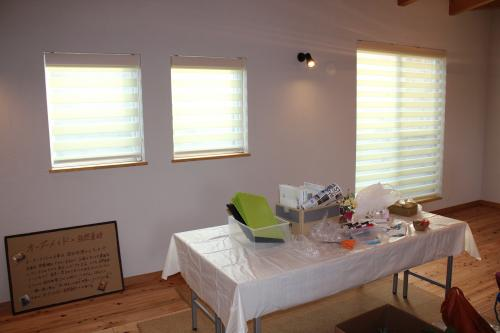 ブラインドが掛かった小窓が2つと大きな窓が1つ。手前にはテーブルが写った写真