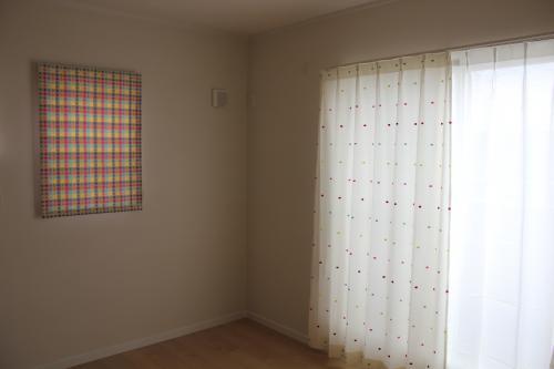 白地に水玉模様のカーテンの大きな窓とチェック柄のカーテンの小さな窓がある部屋