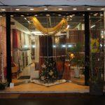 店の外観写真、日が暮れて照明が輝く店内にはクリスマスツリーが飾られている