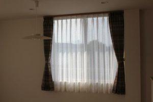 茶色のボーダー柄と白レースのカーテンの掛かった窓