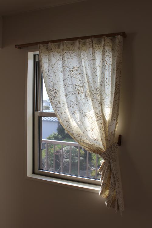 葉っぱ模様のカーテンの掛かった小窓