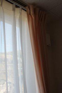 ピンクと白レースのカーテンが掛かった窓のアップの写真