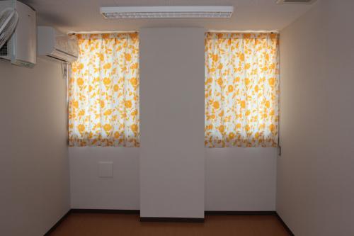 白地に黄色の花柄のカーテンの2つの窓