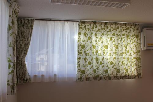 白地に緑の花柄のカーテンの窓