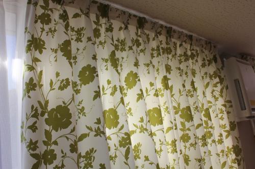 白地に緑の花柄カーテンのアップの写真