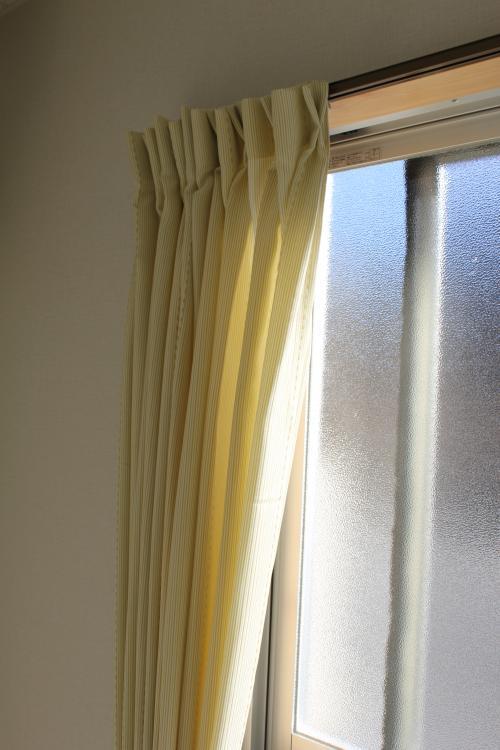 薄黄緑のカーテンが掛かった窓のアップの写真