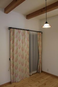 ベージュにピンクの花柄カーテンが掛かった窓がある洋室