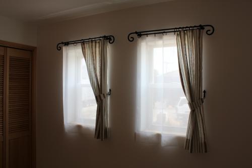 ブルーと淡いブラウンのストライプのカーテンが掛かった2つの窓