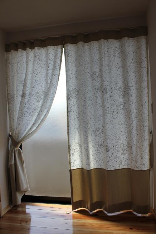 リーフ柄の生地と無地の生地を選び縫い合わせたカーテンが掛かった窓
